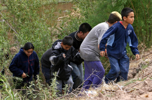TO GO WITH AFP STORY: MEXICO-MIGRATION - An entire family emerges from the bushes on the Mexican bank of the Rio Bravo --reduced in that particular point to a narrow stream-- 11 April, 2006 near Ciudad Juarez, Mexico. Thousands of illegal immigrants cross the border to enter the United States every day in search of better opportunities. AFP PHOTO/Omar TORRES (Photo credit should read OMAR TORRES/AFP/Getty Images)