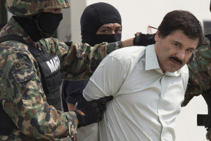 """Bloomberg's Best Photos 2014: Drug trafficker Joaquin """"El Chapo"""" Guzman is escorted to a helicopter by Mexican security forces at Mexico's International Airport in Mexico city, Mexico, on Saturday, Feb. 22, 2014. Mexico's apprehension of the world's most-wanted drug boss struck a blow to a cartel that local and U.S. authorities say swelled into a multinational empire, fueling killings around the world. Photographer: Susana Gonzalez/Bloomberg via Getty Images"""