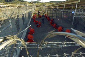 """Detainees in orange jumpsuits sit in a holding area under the watchful eyes of military police during in-processing to the temporary detention facility at Camp X-Ray of Naval Base Guantanamo Bay in this January 11, 2002 file photograph. A cache of classified U.S. military documents provides intelligence assessments on nearly all of the 779 people who been detained at the Guantanamo Bay prison in Cuba. The secret documents, made available to The New York Times and several other news organizations, reveal that most of the 172 remaining prisoners have been rated as a """"high risk"""" of posing a threat to the United States and its allies if released without adequate rehabilitation and supervision, the newspaper said in its report late on April 24, 2011.  REUTERS/Stringer/Files (CUBA - Tags: CRIME LAW POLITICS) - RTXL0IH"""